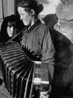 Woman Playing a Russian Button Accordion as Her Young Girl Looks On Premium Photographic Print by Margaret Bourke White