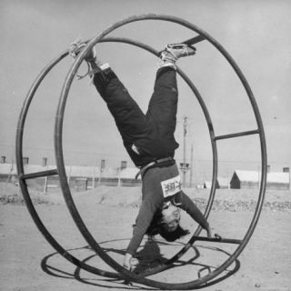 Girl Rolling in Large Wheel During Physical Education Class at North China Union University Photographic Print by George Lacks