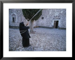 A nun pulls on ropes in a courtyard at the Nea Moni Monastery Pre made Frame